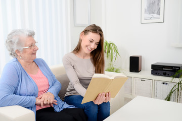 cheerful young woman reading book for elderly senior woman at home