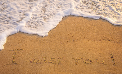 """Dramatic inscription """"Miss You"""" on wet golden beach sand in suns"""
