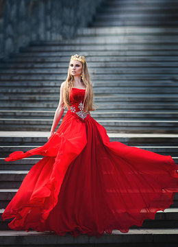 Queen in red dress standing on the stairs