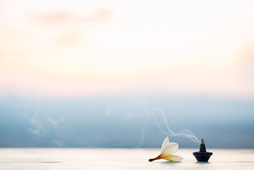 Smoke incense cones with plumeria flower on sunset