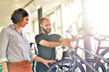 junge Frau schaut sich Fahrräder in einem Geschäft an und wird von einem Verkäufer beraten