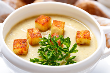 Vegetable soup with pieces of toasted bread and parsley.
