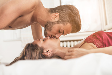 Lovers kissing in bed