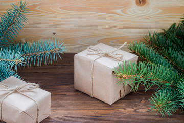 christmas gifts packaged in kraft paper,  jute rope constricted  on wooden table with Christmas tree, free space for text