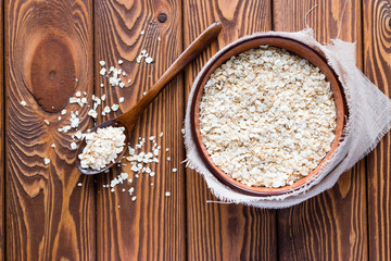 oatmeal in a cup and scattered next to a wooden spoon