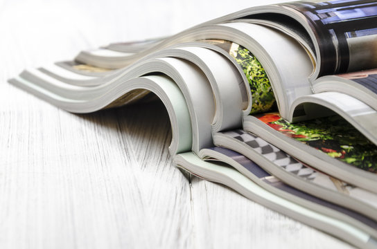 stack of magazines on a white wooden background