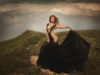 beautiful girl in a black dress in the middle of the field