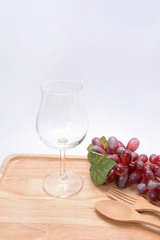 glass and grapes on a wooden floor.