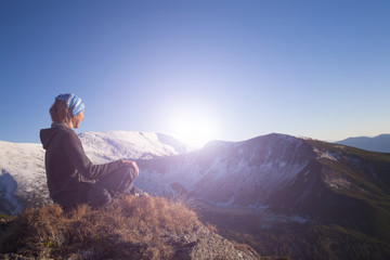 Girl meditates in the mountains.