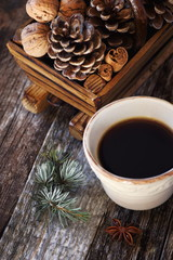 Ñup of coffee, pine cones in basket, walnuts and cinnamon sticks