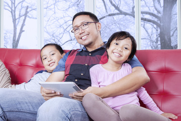 Cheerful kids and dad with tablet smiling at camera