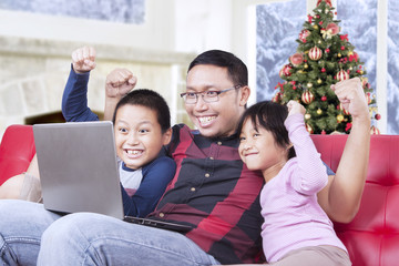 Cheerful kids playing game with dad on laptop