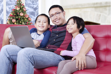 Cute children and dad with laptop on sofa