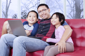 Dad and his children with laptop smiling at the camera