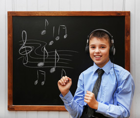 Young cute schoolboy wearing headphones at the blackboard with musical notes