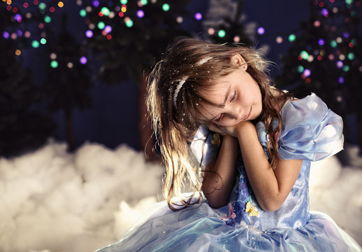 Young princess sits in a forest in a dress