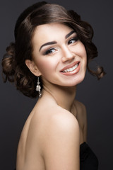 Beautiful brunette girl with perfect skin, evening make-up, wedding hairstyle and accessories. Beauty face