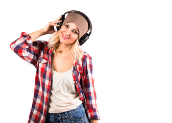 Young hipster woman in headphones posing in studio with white background