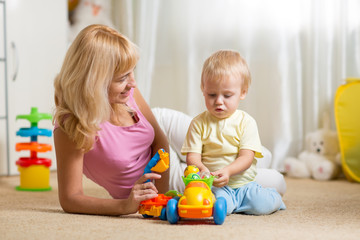 Mother and toddler son play with toy car on nursery floor