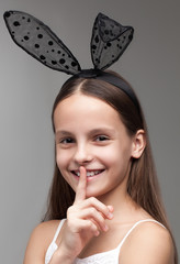 Beautiful little girl with dark hair with black bunny ears on her head posing in the studio on a grey background.