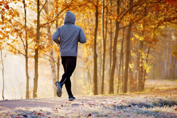 Young man running in the park during autumn morning
