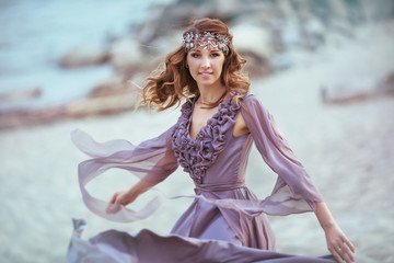 A beautiful girl in a fairy light dress on a coast