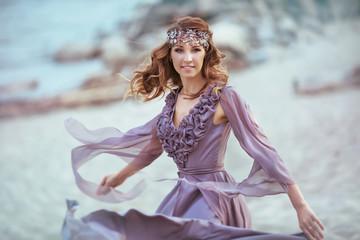 A beautiful girl in a fairy light dress on a coast