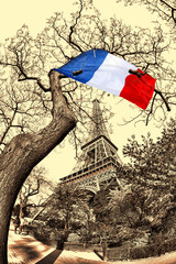 Eiffel Tower with French flag flying on the tree in France