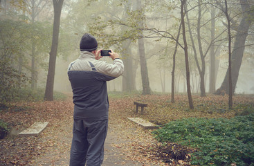 Man take a picture with his phone in the forest