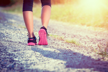 Female athlete runner. closeup on shoe. woman fitness sunset jog workout concept.
