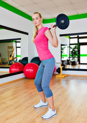 Young woman lifting a barbell in the gym
