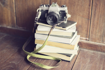 Pile of books with old style camera on wooden floor