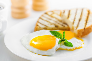 Fried eggs with toasts. Traditional food for breakfast.