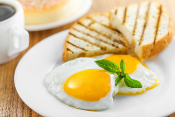 Breakfast with fried eggs, coffee and dessert on table. Healthy food.