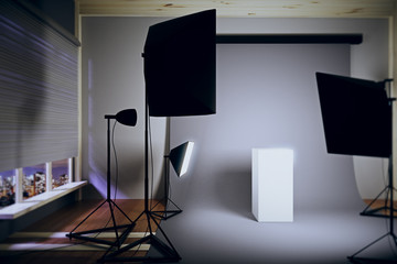 Interior photo studio at night with a white pedestal