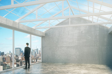 Businessman in empty loft interior room with city view, grey wal
