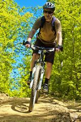 Senior man coming down the mountain on a bike