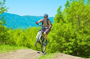 Senior man rides uphill  on a bike