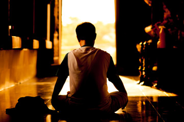 Silhouette of a beautiful Yoga man in the temple.art tone