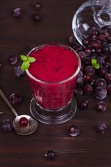 Frozen summer berries smoothie garnished with mint on dark wooden background