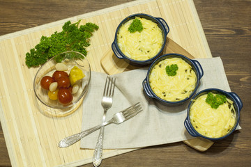 Julienne with mushrooms and cream. Mushroom and cheese gratin in ceramic bowls, on wooden background