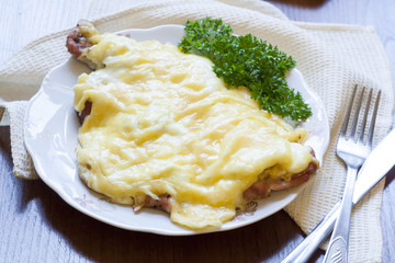 Baked pork chops with onion, mayonnaise cheese with fresh parsley on plate