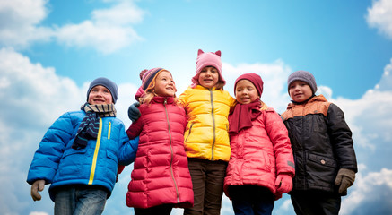 happy children hugging over blue sky background