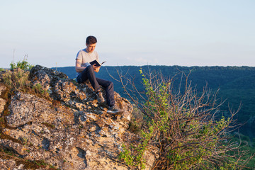 man sits on the cliff and reading a book