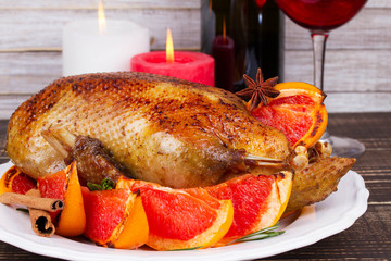Festive Christmas duck baked with grapefruit and rosemary, glass and bottle of red wine; candles