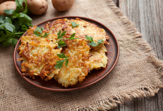 Traditional potato pancakes or latke homemade jewish food Hanukkah celebration recipe. Homemade organic vegan meal in clay dish on vintage wooden background