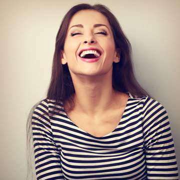 Happy natural laughing young casual woman with wide open mouth a