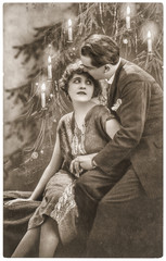 Young couple in love celebrated with christmas tree. Vintage pic