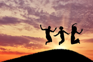 Silhouette of a happy group of people jumping