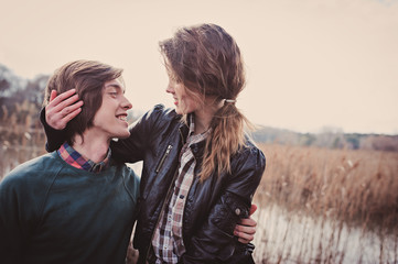 young loving happy couple on cozy warm outdoor walk on country side